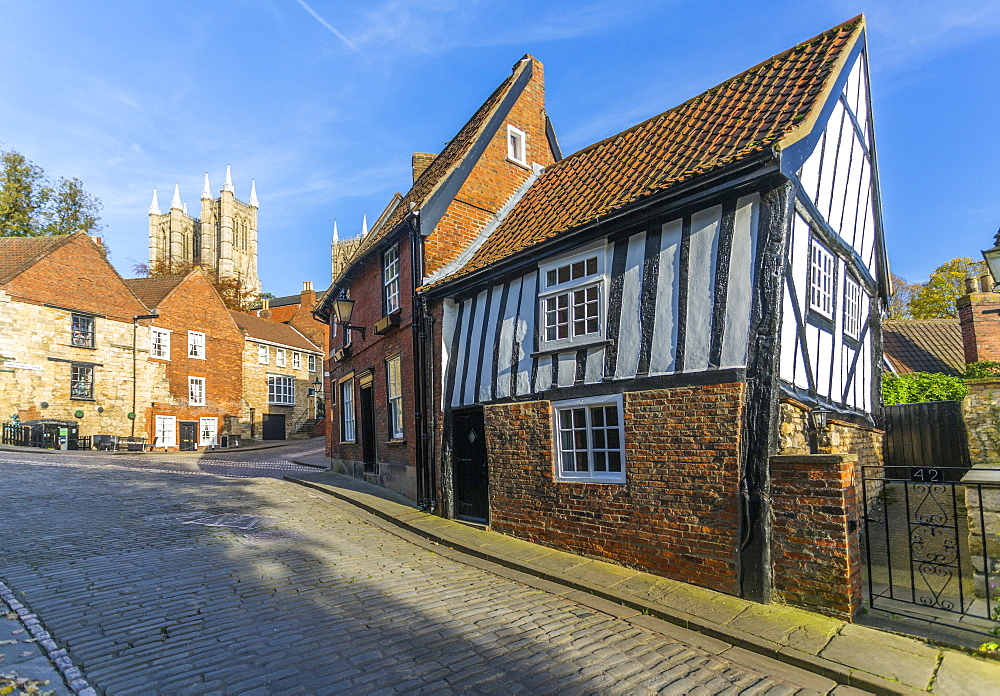Lincoln Cathedral and timbered architecture viewed from the cobbled Steep Hill, Lincoln, Lincolnshire, England, UK, Europe