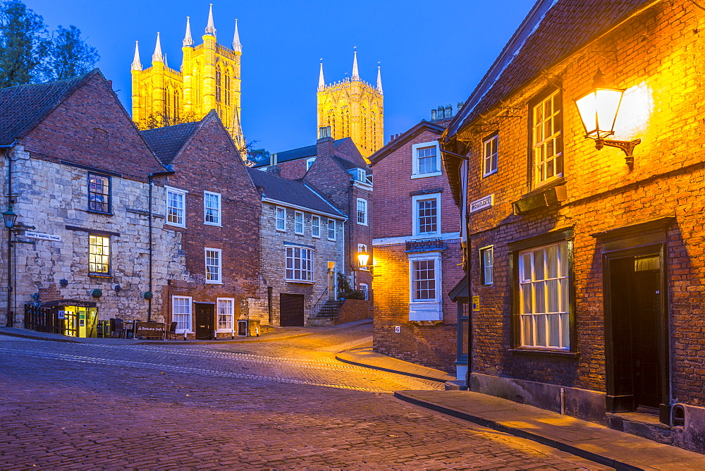 View of illuminated Lincoln Cathedral viewed from the cobbled Steep Hill at dusk, Lincoln, Lincolnshire, England, UK, Europe - 844-14475