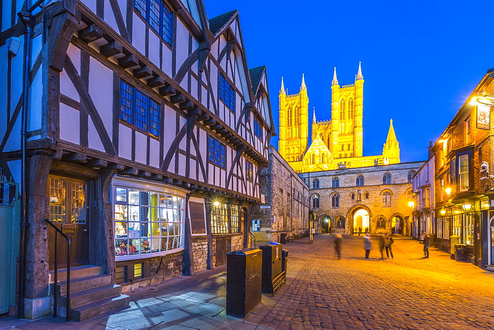 View of illuminated Lincoln Cathedral viewed from Exchequer Gate with timbered architecture of Visitors Centre at dusk, Lincoln, Lincolnshire, England, UK, Europe