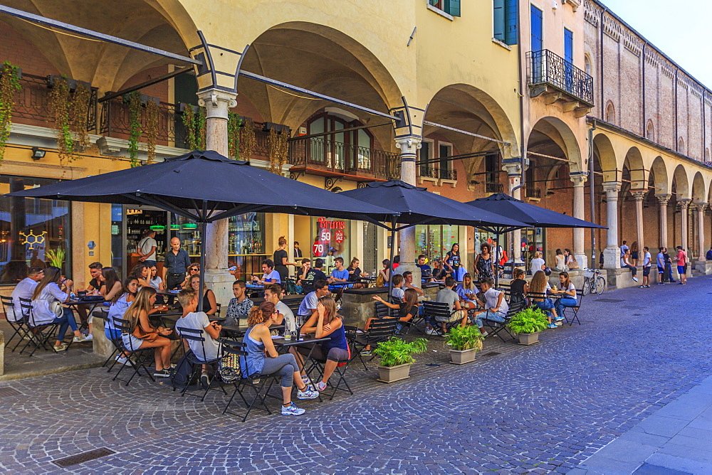 View of pastel coloured architecture, pedestrians and cafe on cobbled street of Via Roma, Padua, Veneto, Italy