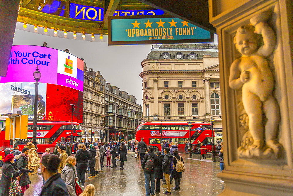 Red buses travelling through Piccadilly Circus and facade of the Criterion Theatre, London, England, UK, Europe