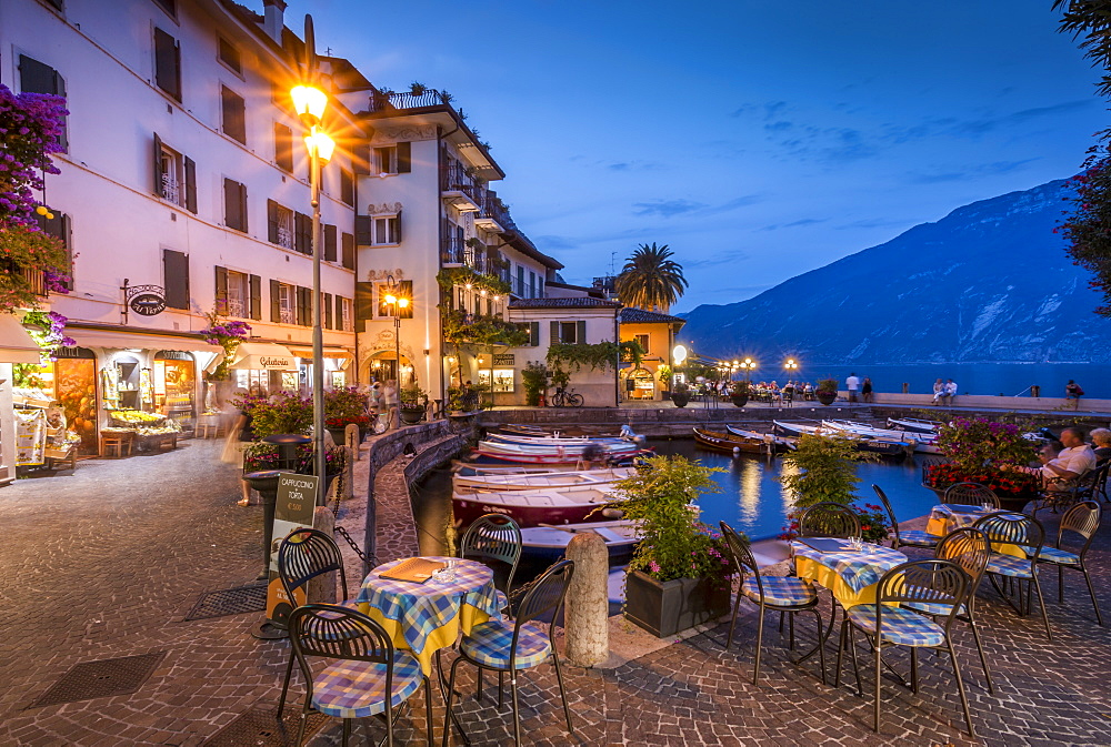View of Illuminated promenade at the port of Limone at dusk, Lake Garda, Lombardy, Italy, Europe