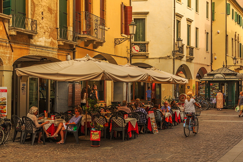 View of cyclist, pedestrians and cafe on cobbled street of Via Roma, Padua, Veneto, Italy