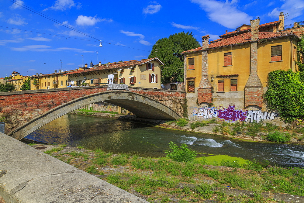 View of pastel coloured properties aligning the river and Ponte San Giovanni delle Navi, Padua, Veneto, Italy