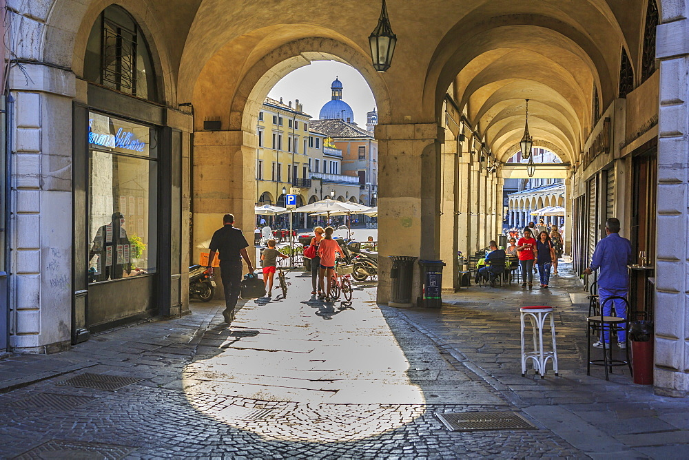View of Piazza delle Erbe through archways and dome of Padua Cathedral visible, Padua, Veneto, Italy, Europe