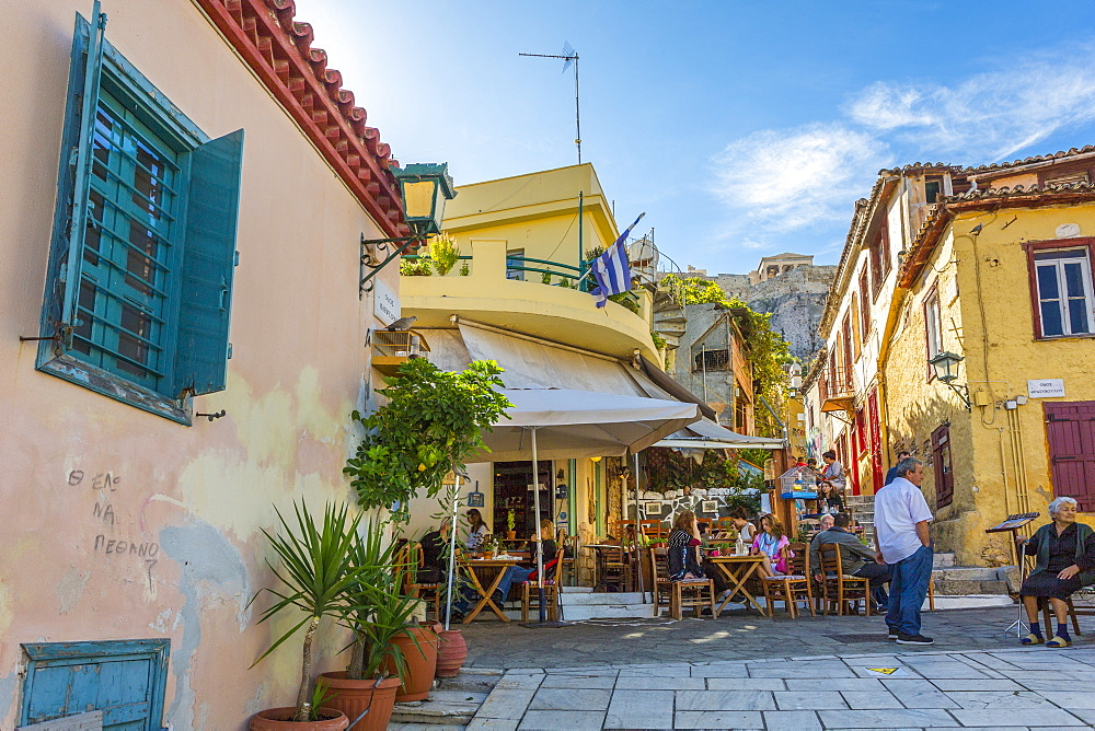 View of pastel coloured houses and cafe in Plaka District of Athens, overlooked by the Acropolis, Athens, Greece, Europe