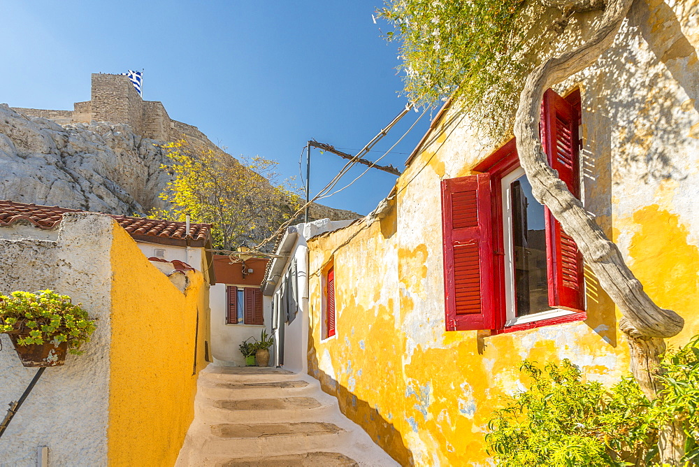 View of pastel coloured houses in Plaka District of Athens, overlooked by the walls of The Acropolis, Athens, Greece, Europe