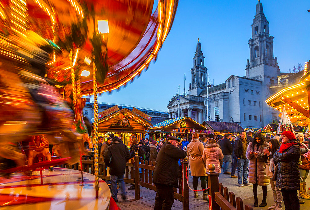 View of carousel and Christmas Market stalls at Christmas Market, Millenium Square, Leeds, Yorkshire, England, UK, Europe