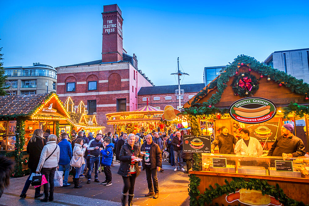 View of visitors and Christmas Market stalls at Christmas Market, Millenium Square, Leeds, Yorkshire, England, UK, Europe