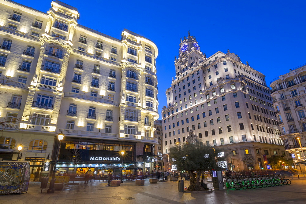 View of architecture illuminated on Gran Via at dusk, Madrid, Spain, Europe