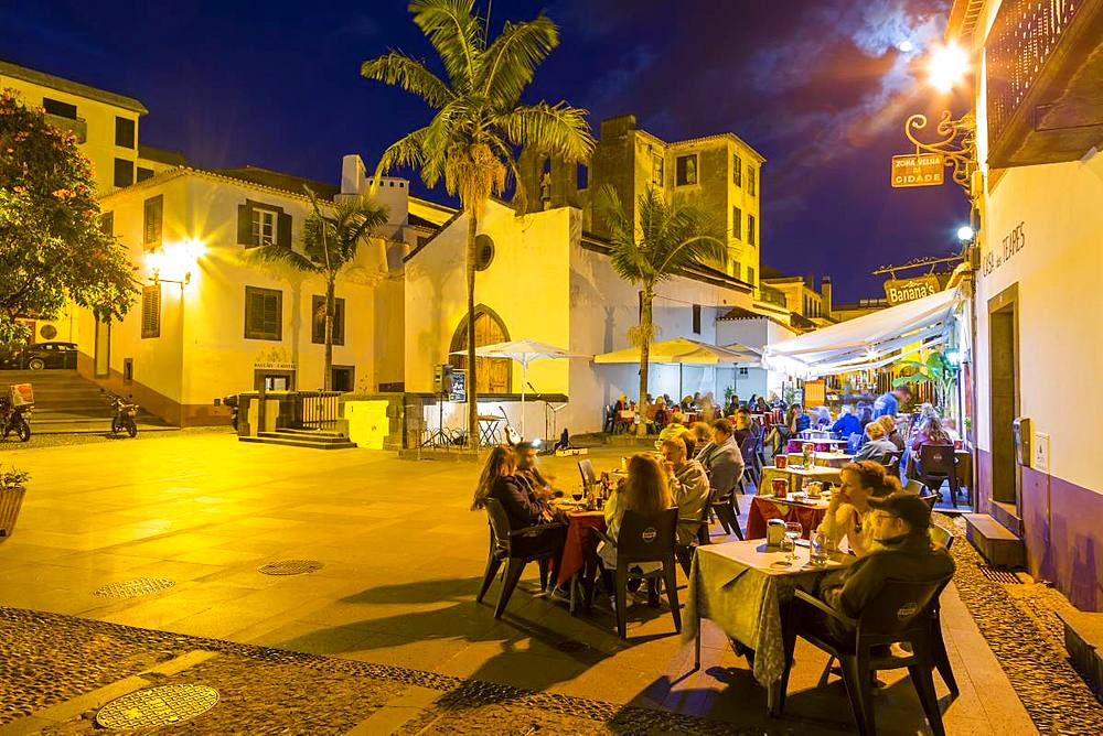 View of cafe in cobbled street in old town at dusk, Funchal, Madeira, Portugal, Europe