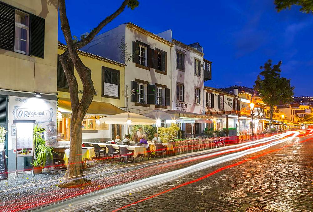 View of cafes and car trail lights in old town at dusk, Funchal, Madeira, Portugal, Europe