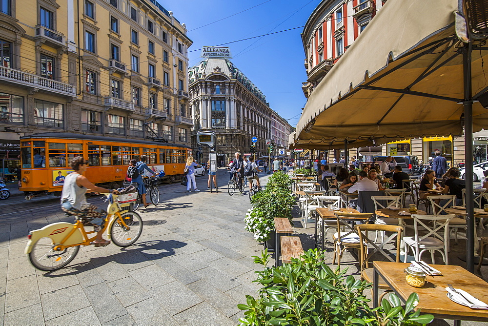 View of restaurant, tram and pedestrians on Via Dante, Milan, Lombardy, Italy, Europe