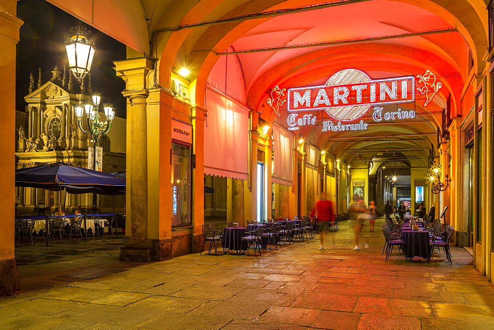 View of Martini Cafe under the arches in shopping arcade at night, Turin, Piedmont, Italy, Europe