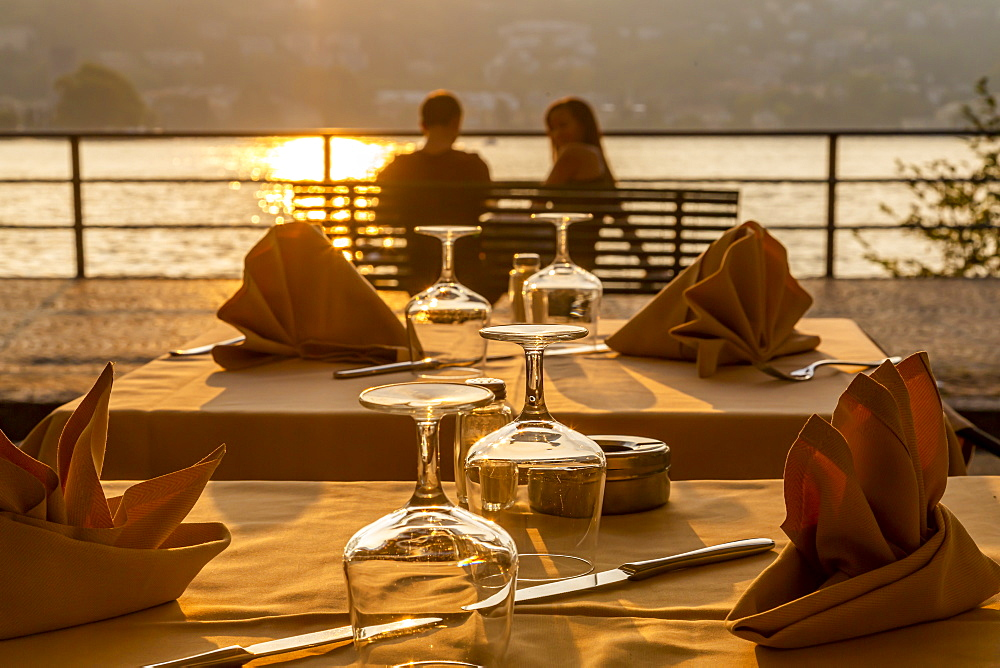 Restaurant tables set for dinner and couple overlooking lake at sunset, Como, Province of Como, Lake Como, Lombardy, Italian Lakes, Italy, Europe