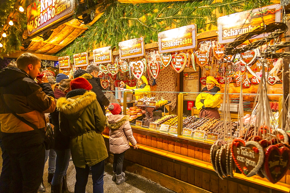 People at Christmas market stall at night in Rathausplaza, Vienna, Austria, Europe