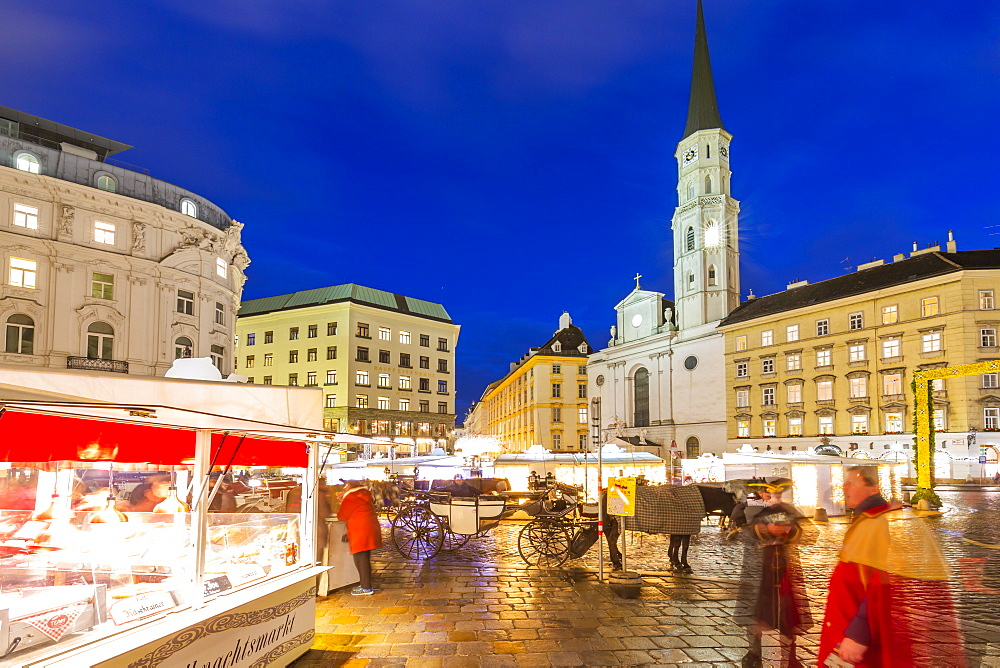 View of Christmas Markets stalls and St. Michael Catholic Church in Michaelerplatz at dusk, Vienna, Austria, Europe