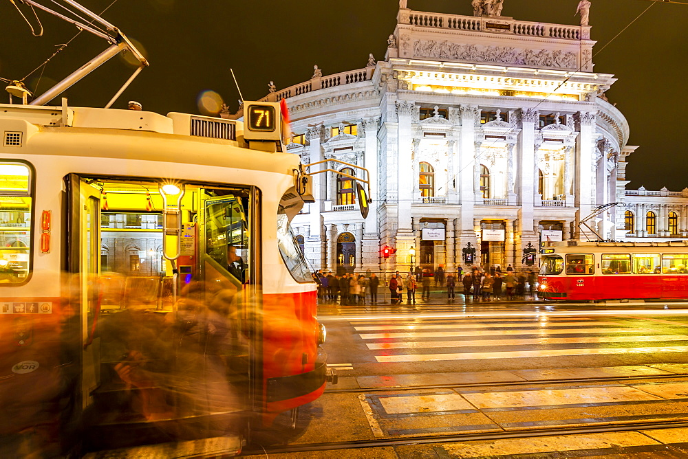 View of Burgtheater and city trams at night in Rathausplaza, Vienna, Austria, Europe