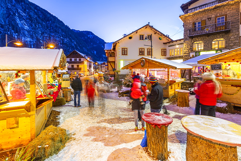 View of Christmas Market stalls at dusk in Campitello di Fassa, Val di Fassa, Trentino, Italy, Europe