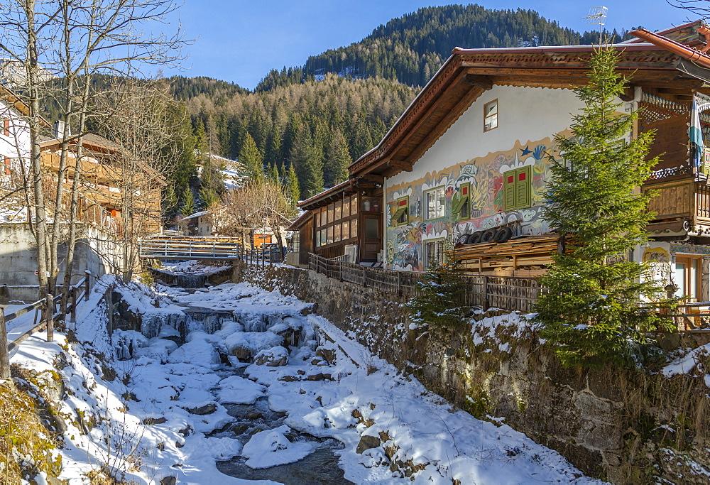 View of frozen river in Canazei town centre in winter, Val di Fassa, Trentino, Italy, Europe