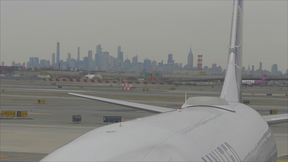 View of airplanes on runway at Newark Airport with Manhattan skyline in background, Newark, New York, United States of America, North America