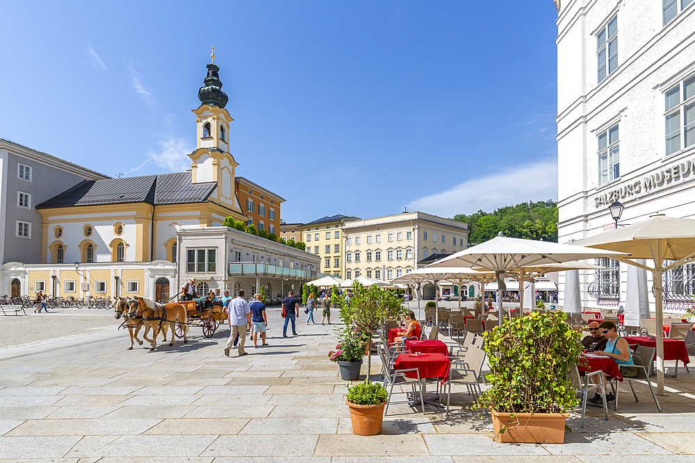 View of St. Michaelskirche and restaurants in Residenzplatz, Salzburg, Austria, Europe