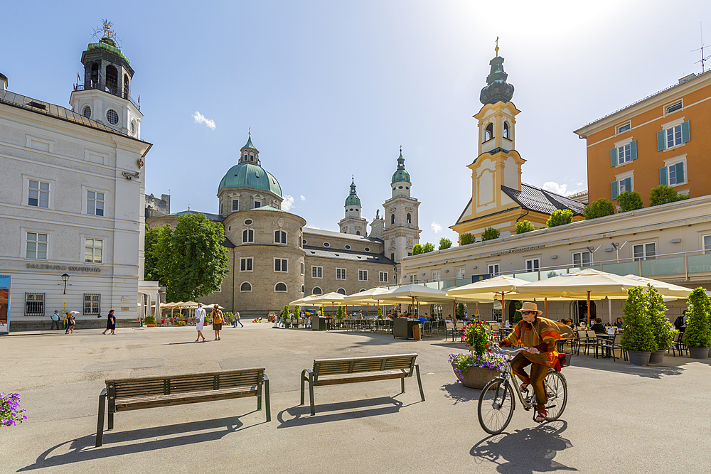 View of cyclist and Salzburg Cathedral in Residenzplatz, Salzburg, Austria, Europe