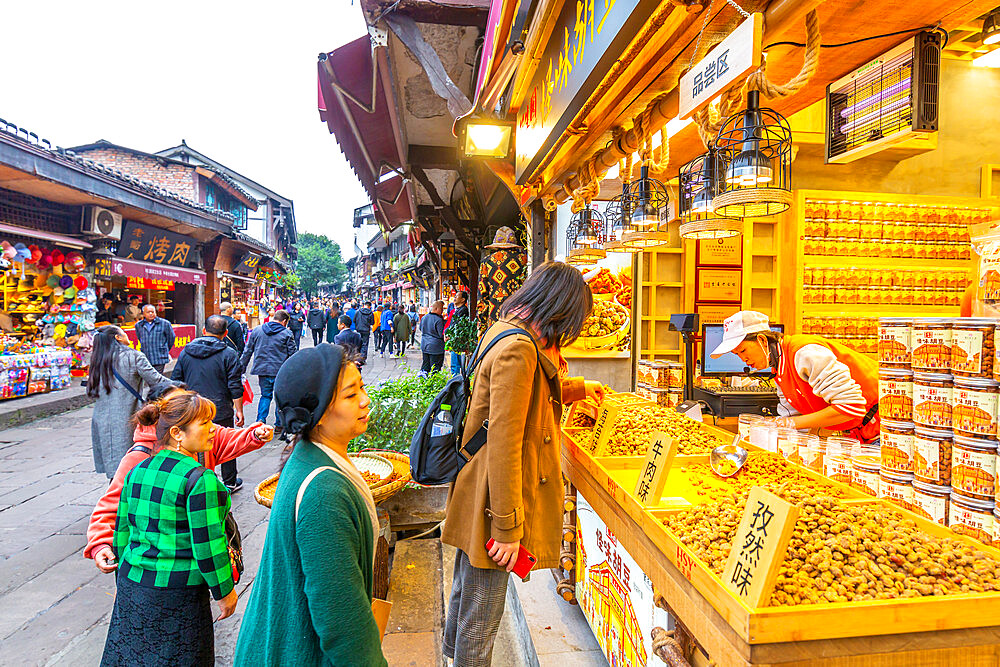 Busy shopping street and local food on display in Ciqikou Old Town, Shapingba, Chongqing, China, Asia