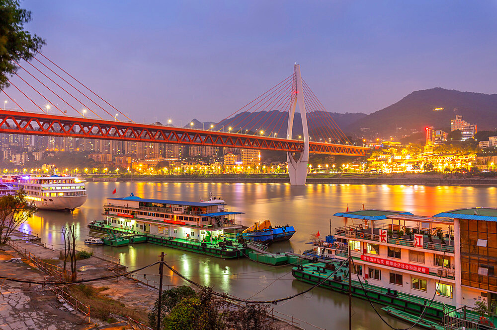 View of Masangxi Bridge and Yangtze River cruise boats at dusk, Yuzhong District, Chongqing, China, Asia