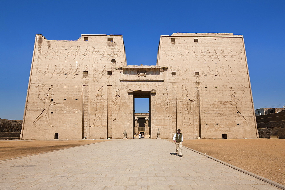 Man standing by the entrance pylon of the Temple of Horus, Edfu, Egypt, North Africa, Africa