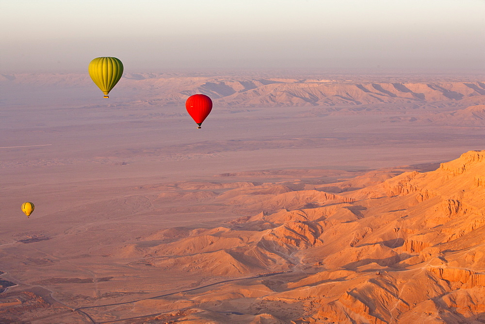 Hot air balloons suspended over the Theban hills of Luxor and the Valley of the Queens at sunrise, Thebes, UNESCO World Heritage Site, Egypt, North Africa, Africa