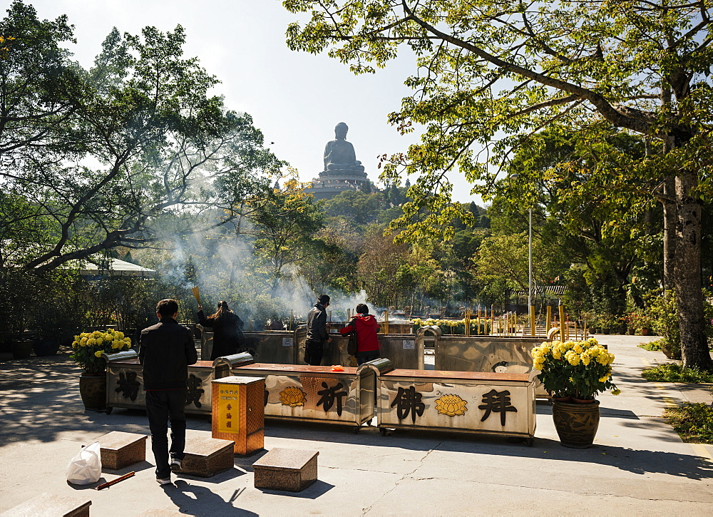 People lighting incense at Po Lin Monastery with Big Buddha statue in background, Lantau Island, Hong Kong, China, Asia