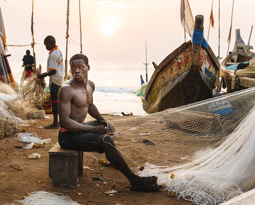 Fisherman fixing nets on beach in Cape Coast, Ghana