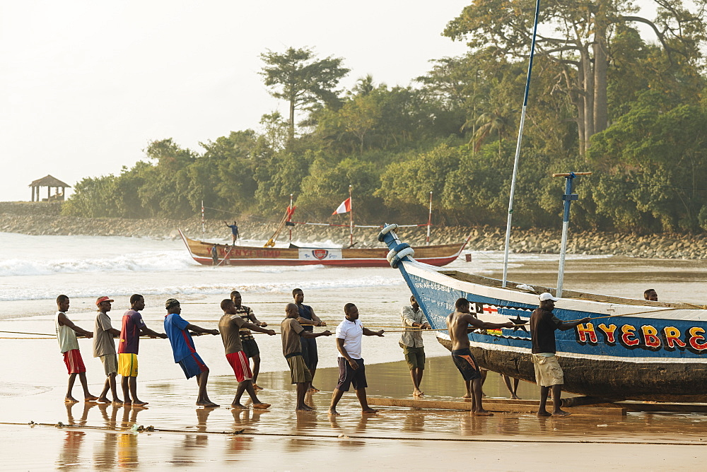 Men pulling boat out to sea, Busua, Ghana, Africa - 848-1737