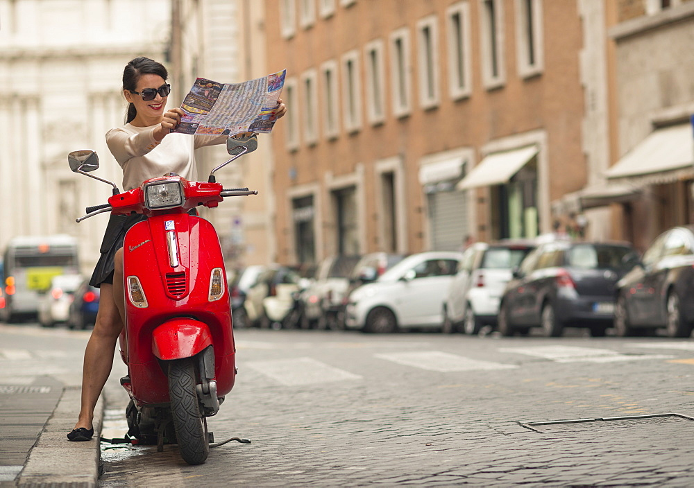 Young woman reading map on a Vespa moped, Rome, Lazio, Italy, Europe