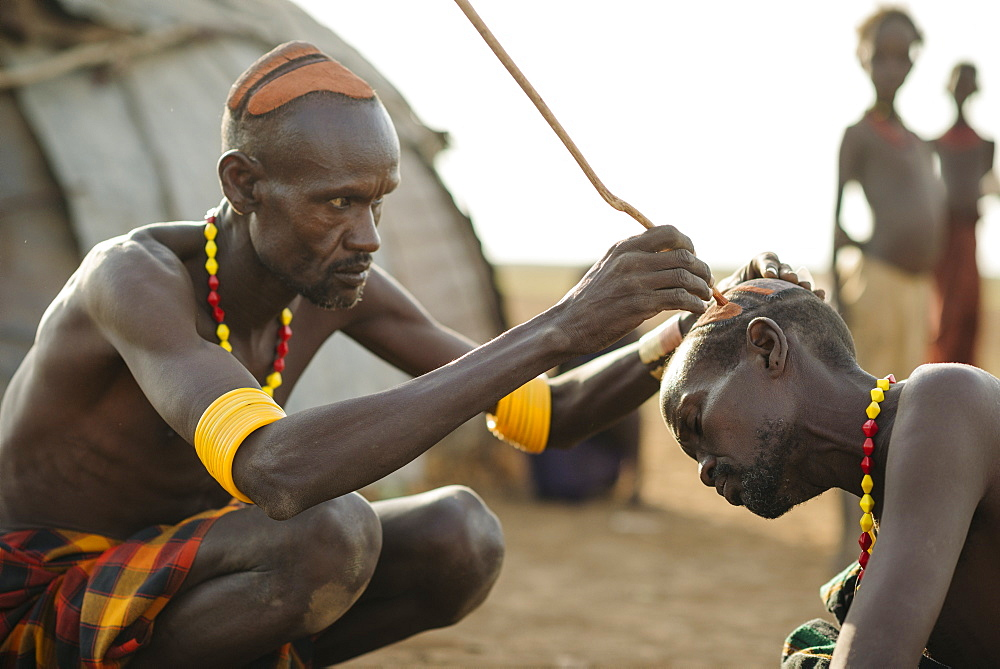 Shuoloch applying clay hair decoration to Chafich, Dassanech Tribe, Salany Village, Omorate, Omo Valley, Ethiopia, Africa