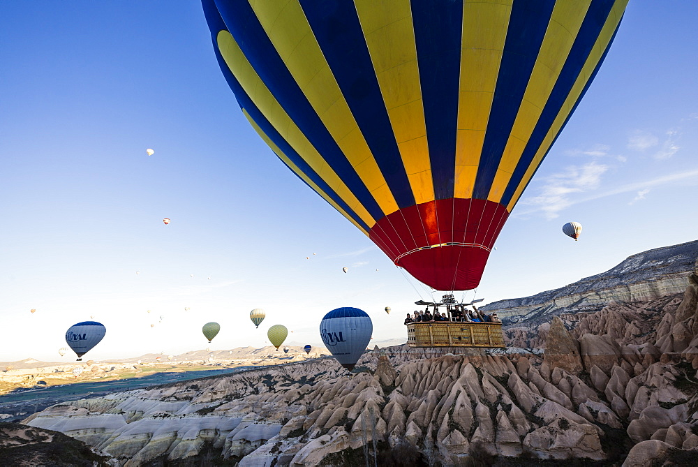 Hot air balloons flying among Rock formations at sunrise in the Red Valley, Goreme National Park, Cappadocia, Anatolia, Turkey, Europe