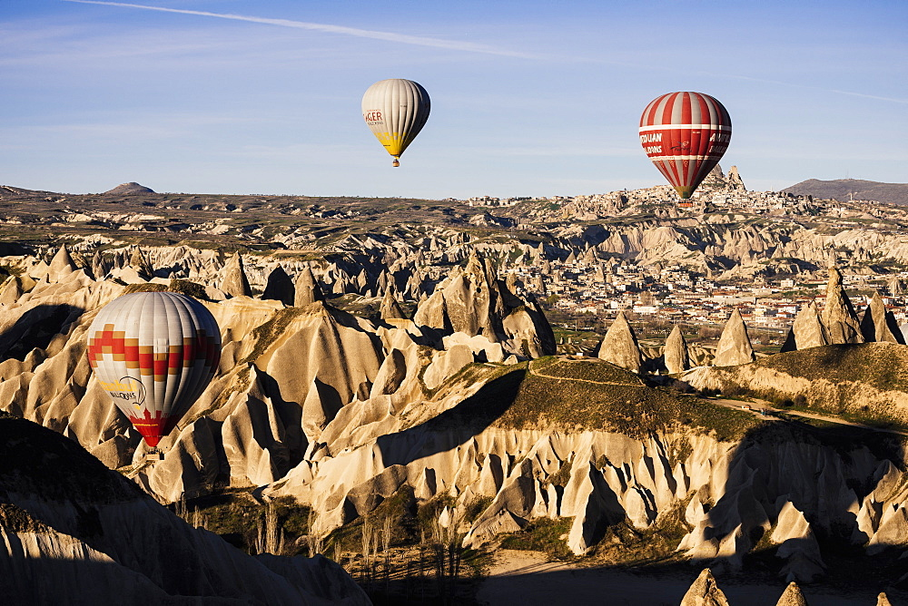 Hot air balloons flying among rock formations at sunrise in the Red Valley, Goreme National Park, UNESCO World Heritage Site, Cappadocia, Anatolia, Turkey, Asia Minor, Eurasia - 848-989