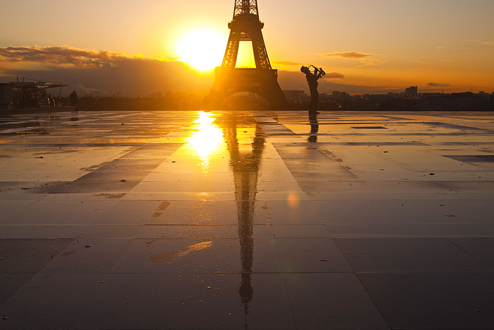 A man playing a trumpet in front of the Eiffel Tower, Paris, France, Europe