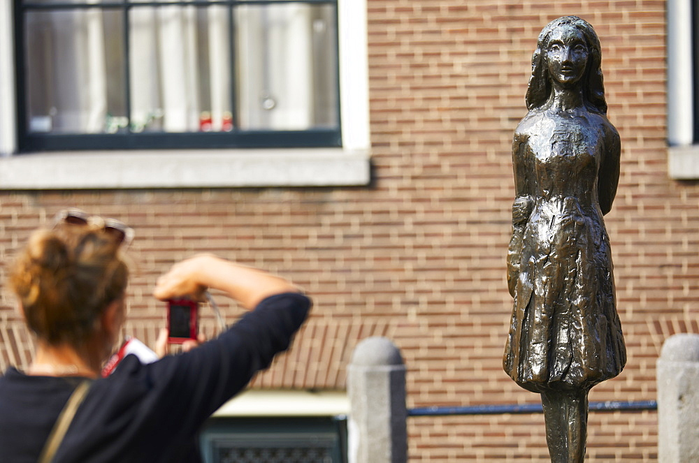 Statue of Anne Frank outside Westerkerk, near the Anne Frank House in Amsterdam, Netherlands. - 851-897