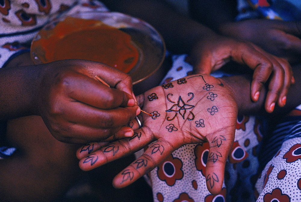Lamu, Kenya. Swahili woman paints henna design on hand of a friend for Idd al Fitr festival.