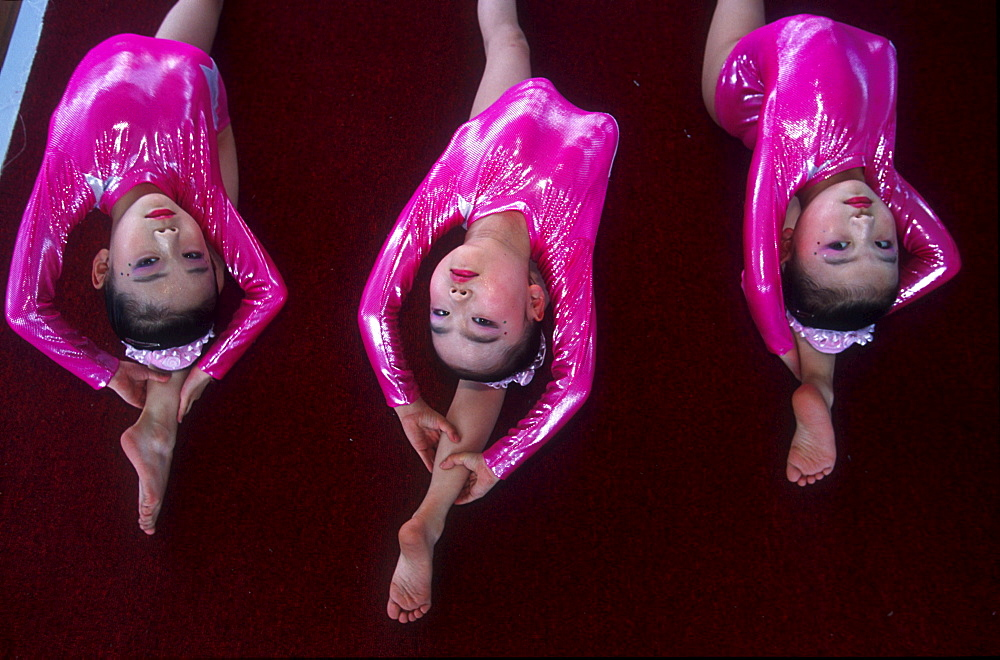 The national gymnastics competition for the under sixes, held in the city of Hangzhou. 60 teams from all provinces of China compete. During this competition, potential olympic talents can be discovered. Three girls are limbering up before the main event.