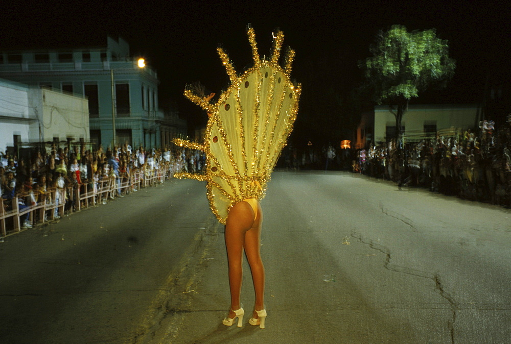 A local dancer waves to the crowd as she leads a float down Av. Victoriano Garzon during the nightly parades of Carnaval in Santiago de Cuba.