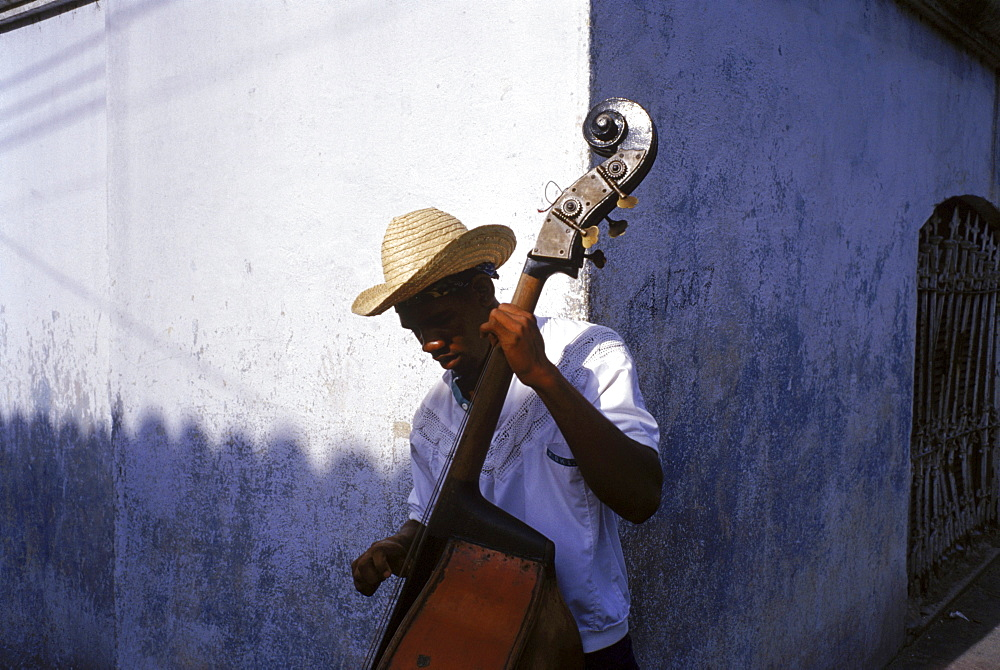 A young musician stops to play some music for tourists and locals as they walk by, hoping to earn some of their change.