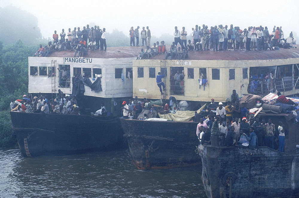 Passengers crowd the decks and roofs of three lead barges pushed up the Congo River by the boat Col. Ebeya.
