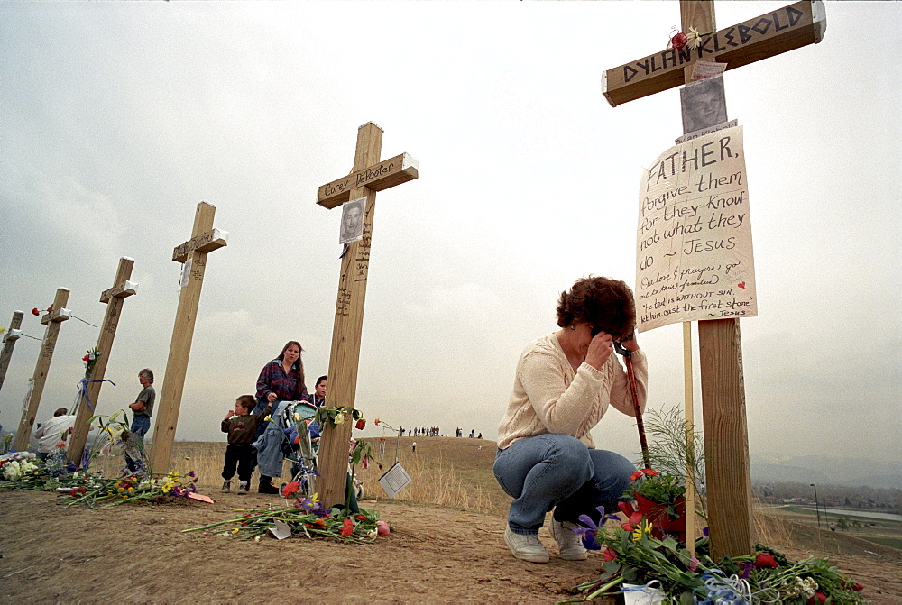 Cindy Fairchild, of Aurora, Colo., prays below a six-foot cross in honor of Columbine shooter Dylan Klebold at Robert F. Clement Park in Littleton. Fifteen identical crosses were planted on a hill in the park, one for each victim of the shootings at Columbine High, including shooters Eric Harris and Dylan Klebold.