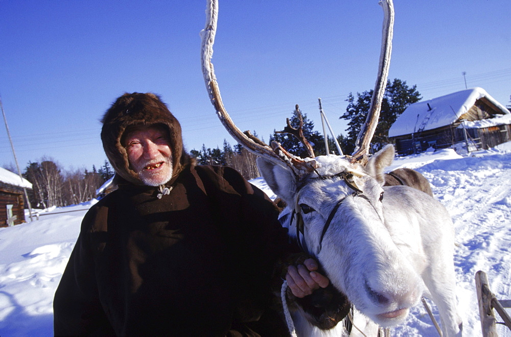 A Khanty reindeer herder with his most prized deer in Houlor. White deer have special significance for the Khanty.