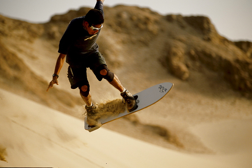 A famous local sandboarder trying to keep his balance 10 feet off the ground in the Ica Desert, Peru on June 25, 2002. Local kids in the Ica Desert, inspired by American snowboard videos, are creating a new sport and riding the highest dunes in the world.