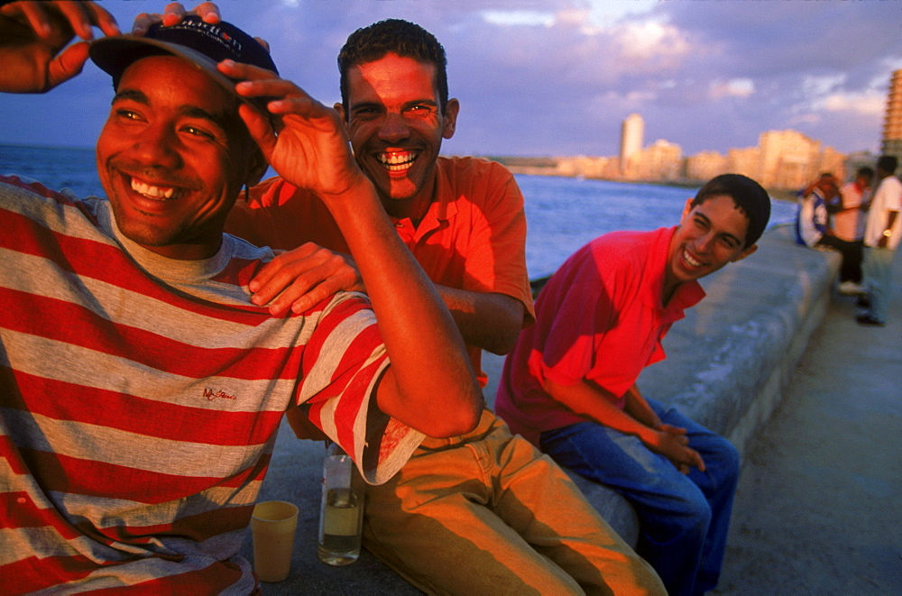 Laughter, music and rum frequently flow on the malecon, Havana, Cuba's main water front street where locals come to watch the sunset and socialize.