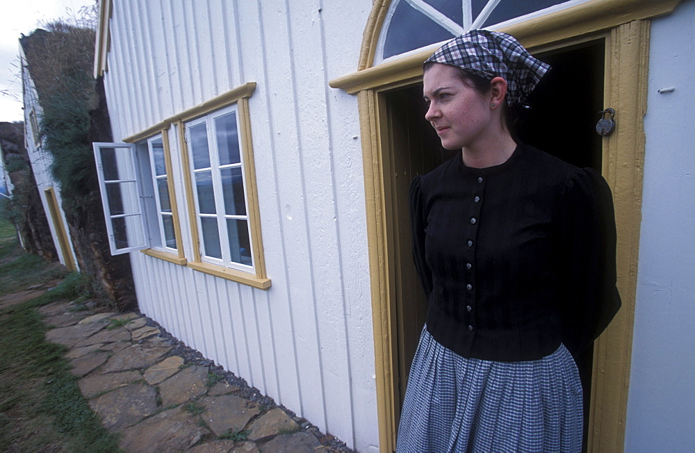 Museum employee in period costume in front of an historic turf building at Glaumbaer, northcentral Iceland. An important discovery was made in Glaumbaer in 2001: the homestead of Thorfinn Karlsefni, the father of the first European born in the New World. This find has important implications for Viking history.